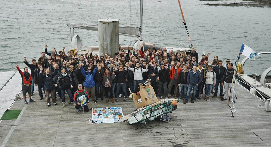 Toute l'équipe de Coriolis composites pose avec son bateau recyclé.
