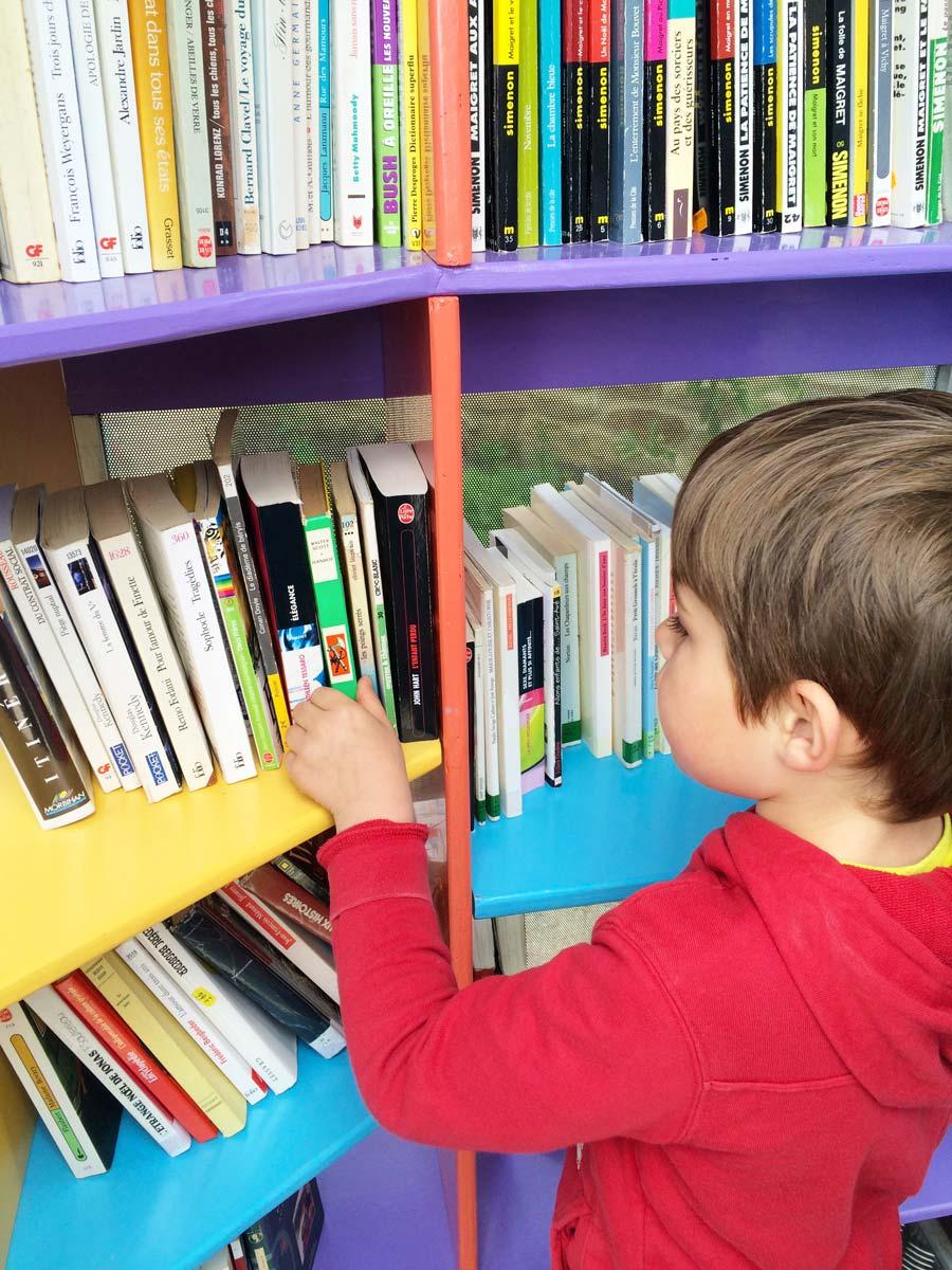 Un enfant choisi un livre dans l'ancienne cabine téléphonique